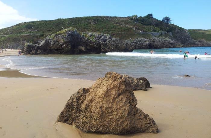 Una de las rocas diseminadas junto a la orilla en la playa de Borizu